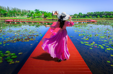 Fototapeta Orientalny Asian women walk on the red wooden bridge to see the beauty of lotus flowers