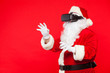 Leinwanddruck Bild - Santa Claus wearing virtual reality goggles, on a red background. Christmas