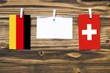 canvas print picture Hanging flags of Germany and Switzerland attached to rope with clothes pins with copy space on white note paper on wooden background.Diplomatic relations between countries.