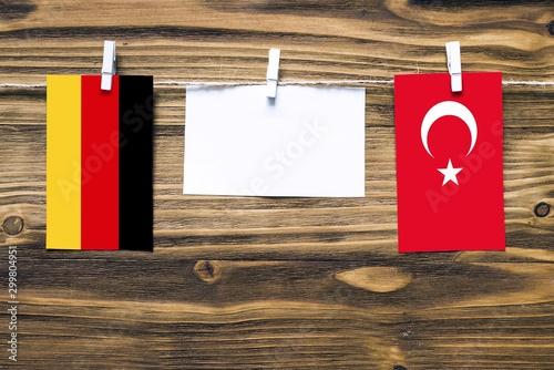 Hanging flags of Germany and Turkey attached to rope with clothes pins with copy space on white note paper on wooden background Wallpaper Mural