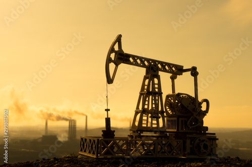 Fototapeta Oil pump on the background of sunset and pipes of the plant. Oil production, natural resources, fuel obraz