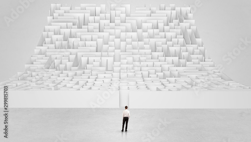 Fotomural  Businessman standing and thinking in front of a curved infinity maze