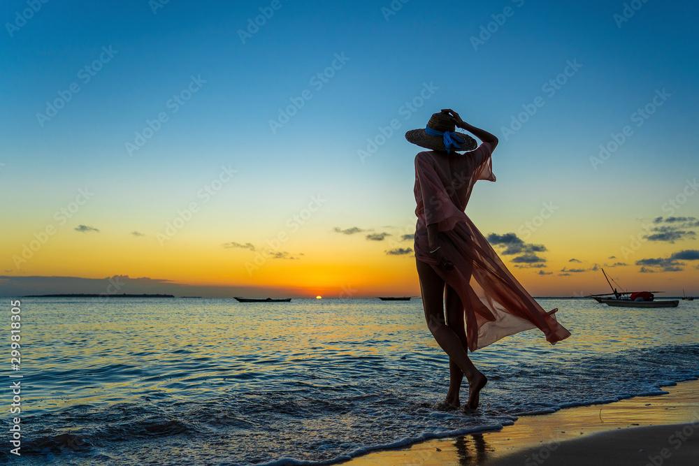 Fototapeta Beautiful girl in a straw hat and pareo on the beach during sunset of Zanzibar island, Tanzania, east Africa