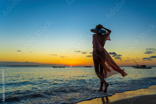 Foto auf Gartenposter See sonnenuntergang Beautiful girl in a straw hat and pareo on the beach during sunset of Zanzibar island, Tanzania, east Africa