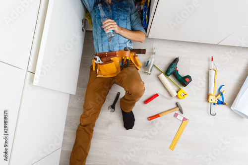 Fotomural  drunk plumber doing sink reparation