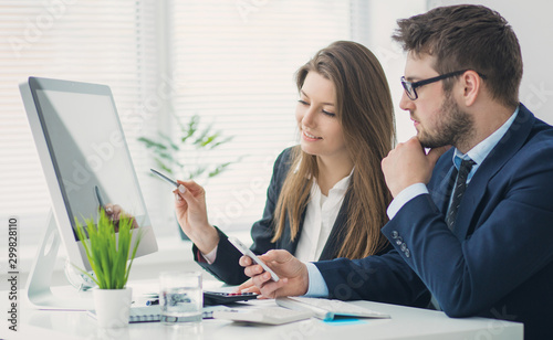 Young businessman discussing something with his colleague, and using a digital t Fototapet