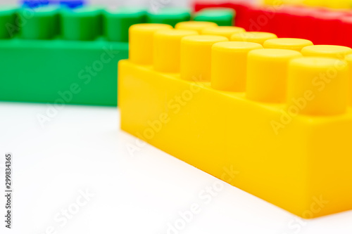 Many colorful toy plastic bricks, kit of blocks for building and constructing with a yellow one close up on white background with copy space