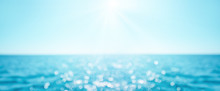 Beautiful Blur Defocused Blue Sea Background With Sun Rays And Bokeh. Landscape Of Tropical Summer. Summer Vacation Concept