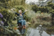 Senior Woman Sitting At Garden Pond, Listening Music