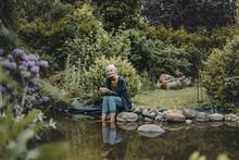 Woman Relaxing At Garden Pond, Drinking Tea