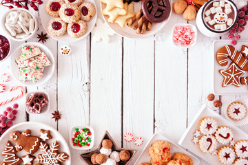 Christmas sweets and cookie frame. Top view table scene over a white wood background with copy space. Holiday baking concept.