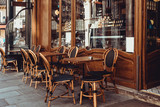 Fototapeta Uliczki - Cozy street with tables of cafe in Paris, France