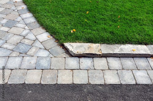 This landscape project shows a professionally designed and crafted transition from walkway to driveway, and uses natural stone curbing to minimize the grade between lawn and pavers Slika na platnu