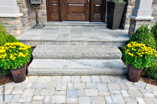 Obraz na plátně Flagstone applied to the original concrete veranda, natural stone steps, and paver walkway all provide a beautiful, fresh landscape update to this stately home