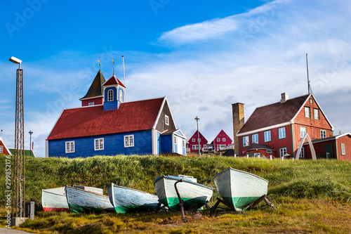 Fishing wooden boats and the blue bethel church in Sisimiut, Greenland Canvas Print