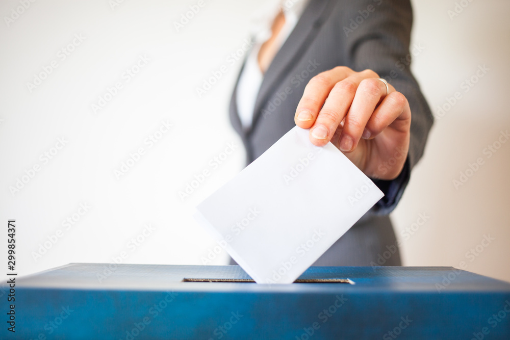 Fototapety, obrazy: elections - The hand of woman putting her vote in the ballot box