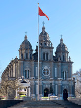 Romanesque Revival Style In Architecture. St. Joseph's Church, Catholic Church In Beijing. Red China Flag In Front Of The Facade. Christmas Tree And Decorations At The Entrance To The Church