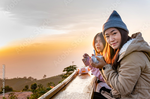 Fényképezés  Two asian woman sits coffee at sunrise on the top of a mountain.