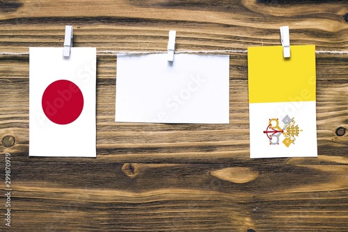 Photo  Hanging flags of Japan and Vatican City attached to rope with clothes pins with copy space on white note paper on wooden background
