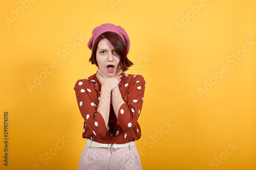 Young beautiful caucasian brunette woman over isolated yellow background shouting, suffocate because painful strangle Wallpaper Mural