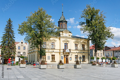 NOWY TARG, POLAND - SEPTEMBER 12, 2019: City hall building and fountain in front of it at the market square - fototapety na wymiar