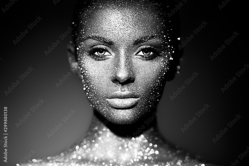 Fototapeta Fashion model woman in bright sparkles and lights posing in studio. Portrait of beautiful sexy woman. Art design glitter glowing make up. Black and white photography
