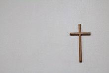 A Wooden Cross On The White Wall Background