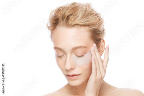 Young woman holding collagen eye patch with one hand, isollated on white background Tablou Canvas