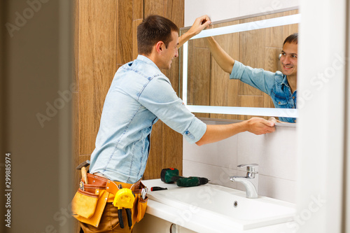 Photo Man installing a mirror on wall in his renewed bathroom