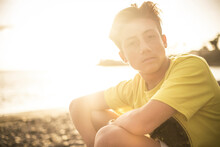 Beautiful Portrait Young Handsome People Male Teenager Looking At The Camera Sitting At The Beach With Sunset Sun In Backlight - Outdoor Leisure Activity Concept