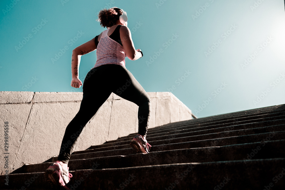 Fototapety, obrazy: Afro American girl in headphones running up the stairs