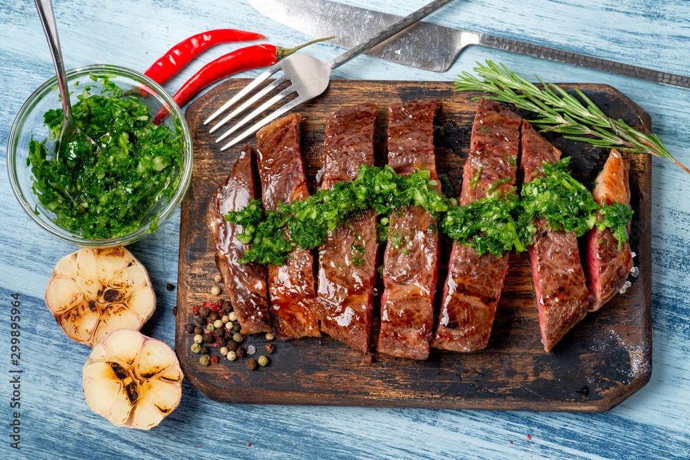 Fototapety, obrazy: Sliced juicy beef steak with chimichurri sauce and spices on wooden board.