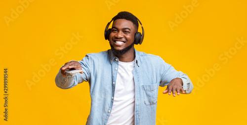 Fotografia Black guy dancing while listening his favorite music in headphones