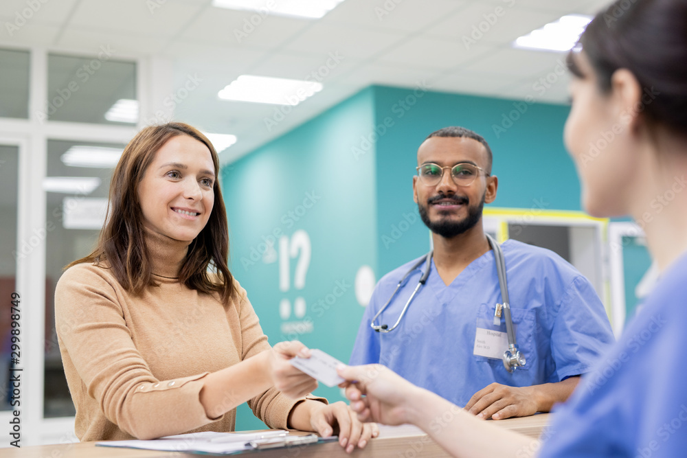 Fototapeta Patient giving credit card to receptionist in clinics to pay for medical service