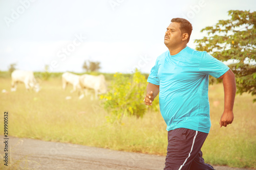 Overweight man running on road - concept of fat man fitness - obese person jogging to reduce the weight Canvas Print
