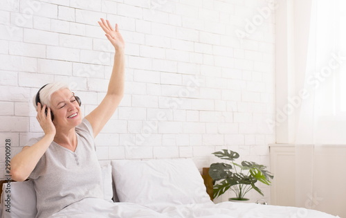 Foto  Playful senior lady in headphones listening to music in bed