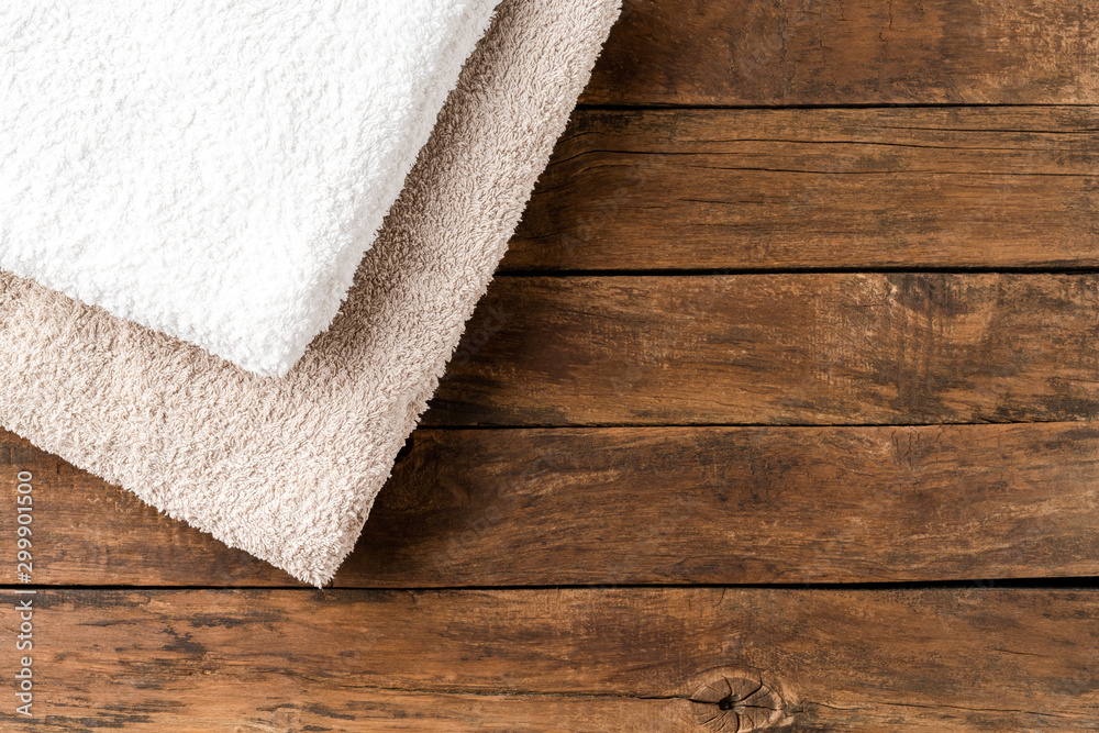 Fototapeta Stack of clean spa towels on rustic wooden background with copyspace. Top view