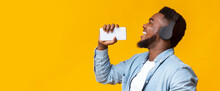 Carefree Black Guy Holding Smartphone And Singing Into It