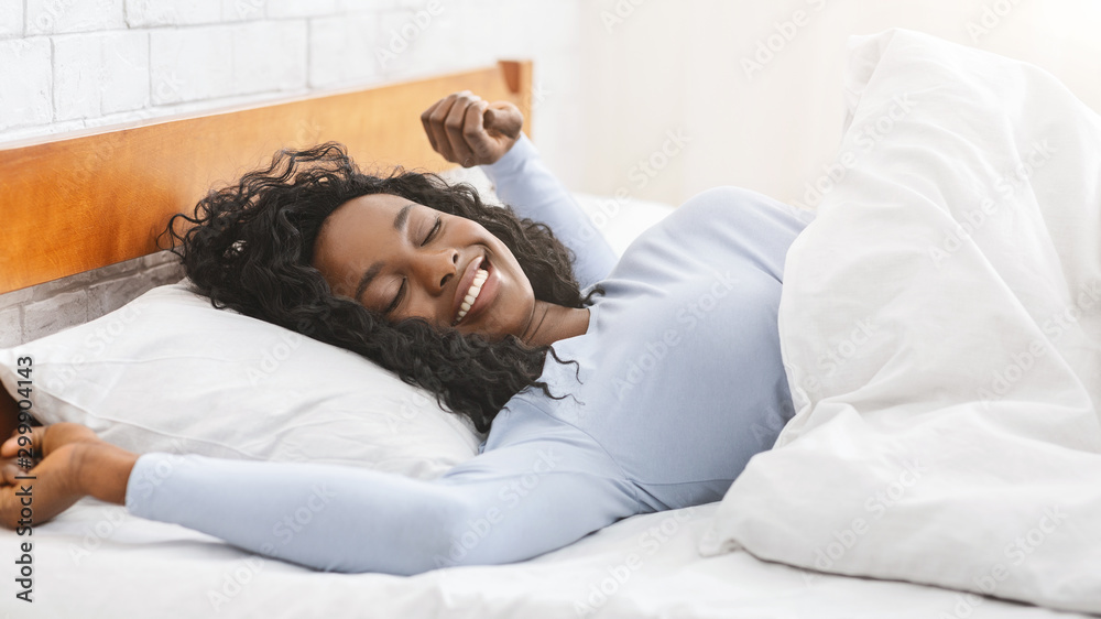 Fototapeta Happy african young woman stretching in bed