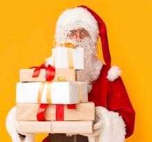 Santa Holding Present Boxes For Children On Orange