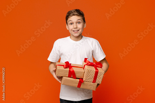 Fotomural  Emotional teenage boy holding lots of holiday gift boxes