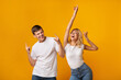 canvas print picture - Carefree young couple dancing on yellow studio background