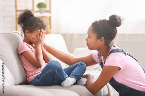 Photo Caring african teen girl calming her sad crying baby sister