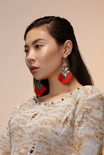Medium Close-up Shot Of A Dark-haired Asian Lady In A Beige Mottled Pullover With Silver Earrings With Embossed Triangular Plates, Oval Insert With Ruby Crystals And A Red Fringe.