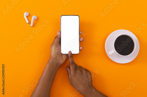 Female hands touching cellphone with blank screen on orange background - 299913927