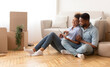 canvas print picture - Spouses Using Tablet Sitting On Floor Among Unpacked Boxes Indoor