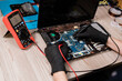 Master of repair service using soldering-irons while working over broken laptop