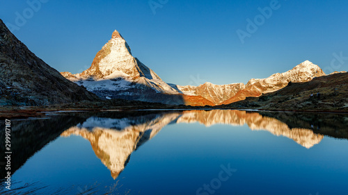 Foto auf Gartenposter Blau Jeans Classical Swiss view of snow-capped epic Mattergorn mountain peak reflected in Riffelsee lake. Iconic landmark in Switzerland located near Zermatt resort. Picturesque landscape of alpenglow in Alps.