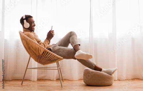 Man In Earphones Using Cellphone Sitting On Chair At Home Tablou Canvas