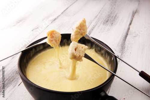 Gourmet Swiss fondue dinner on a winter evening with assorted cheeses on a board alongside a heated pot of cheese fondue with two forks dipping